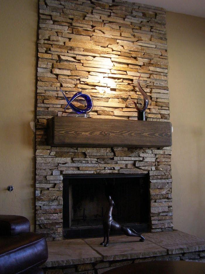 cheminée entouré de mur en plaques de pierre de parement déco avec poutre étagère en bois rectangulaire et objets sculptures en verre soufflé décoratives
