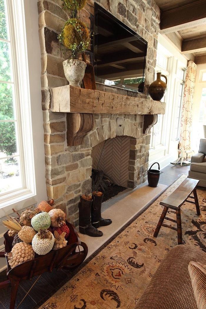 cheminée style ancien en pierre de parement avec mortier à la chaux et étagère en bois vintage, poterie et tv dans salon à décoration rustique