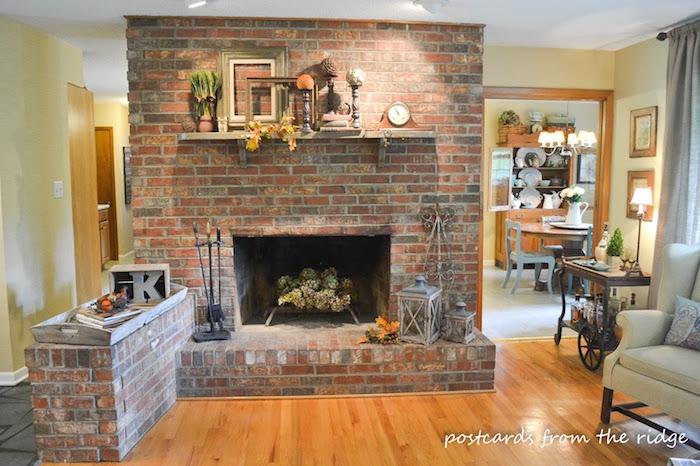 cheminée dans mur séparateur de pièce cuisine salon en briques rouges et déco avec objets anciens