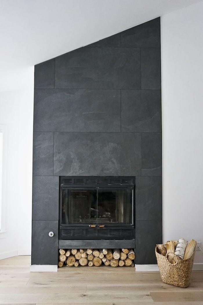 décoration mur et contours de cheminée avec plaques gris anthracite sur mur blanc et sol en parquet clair