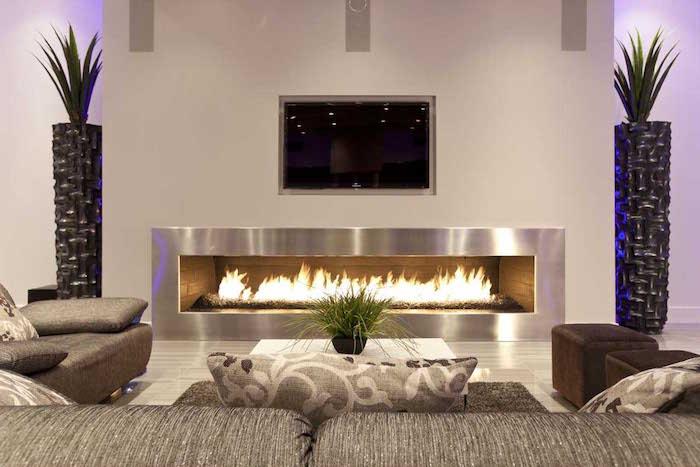 fausse cheminée décorative au gaz style bruleur rectangulaire moderne avec manteau en métal gris dans salon design