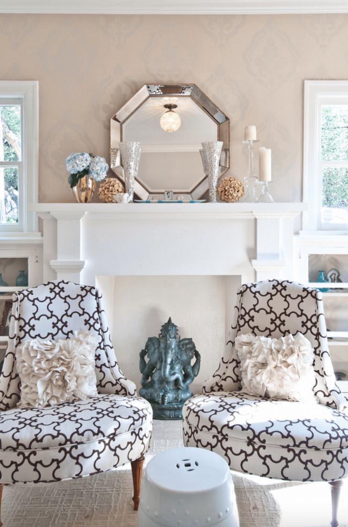manteau de fausse cheminée décorative blanc comme support objets déco bougeoirs, plateau miroir, fauteuils rétro design brodés avec coussins vintage