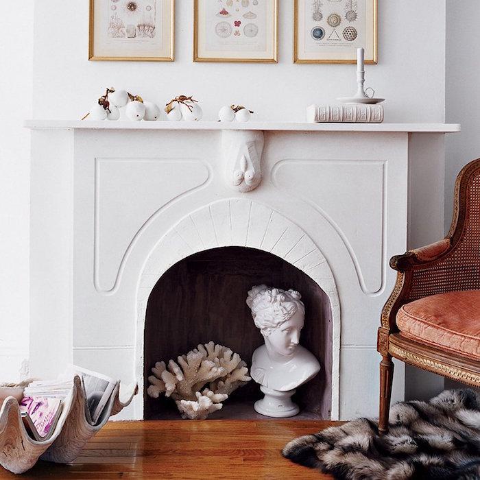 manteau cheminée sculpté en platre avec tete de hibou inversée comme support déco avec statuette et corail dans foyer, boules de coton dessus, salon avec parquet ciré, fauteuil ancien en cuir