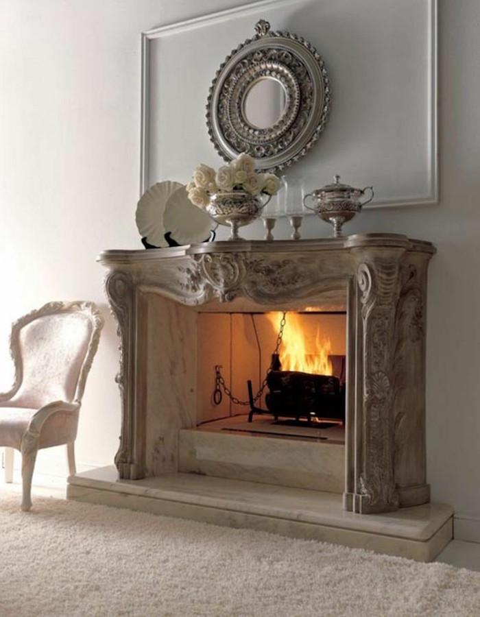 salon à décoration classique vintage avec manteau de cheminée sculpté et objets argenterie décoratifs sur mur blanc