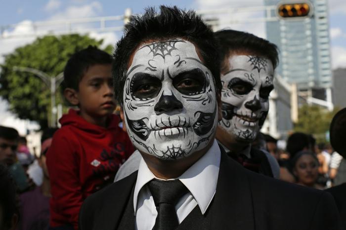 participants au carnaval des morts mexicain, tête de crane dessiné sur le visage d'un homme, cravate noire