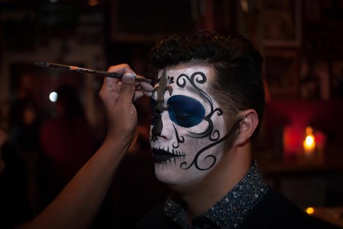 maquillage tete de mort, dessins noirs sur peinture blanche, contours des yeux bleus