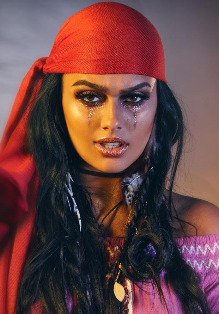 un joli maquillage femme pirate dans les tons bronze avec des yeux charbonneux, femme pirate sauvage avec un foulard rouge