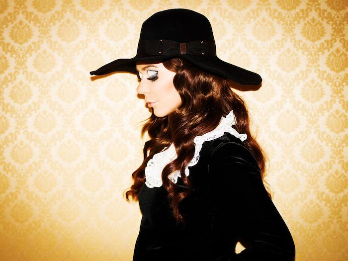 idée intéressante de maquillage de sorcière pour halloween paupières ombres bleues avec contour pli oeil noir, eye liner noir, cheveux bouclés, capeline noire, robe noire à col blanc