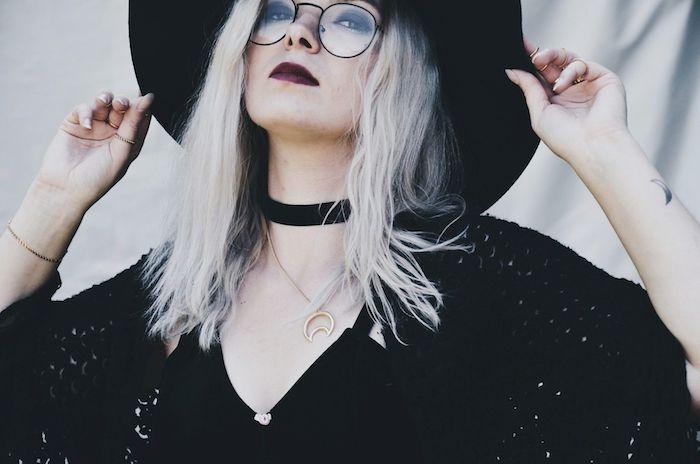 accessoire de sorcière collier ras du cou, gilet à grosses mailles noire, lunettes de vue monture ronde, coloration blond platine, rouge à lèvres rouge, maquillage sorciere halloween