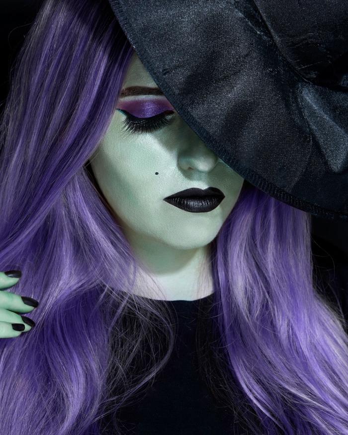 un maquillage sorciere halloween glamour avec visage peint en vert, des yeux fardés de violet et une bouche noire mat