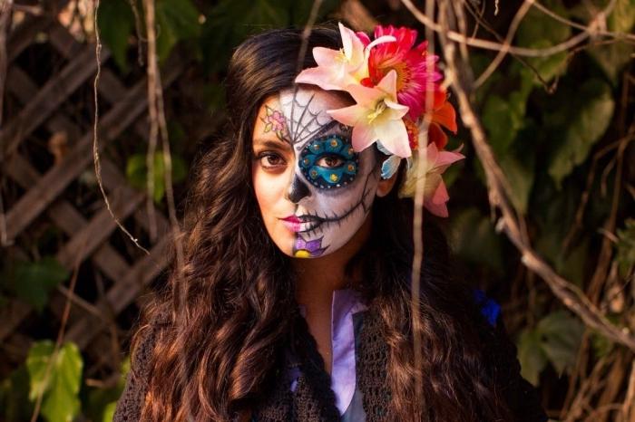 un maquillage tête de mort mexicaine réalisé sur la moitié du visage et coiffure avec fausses fleurs