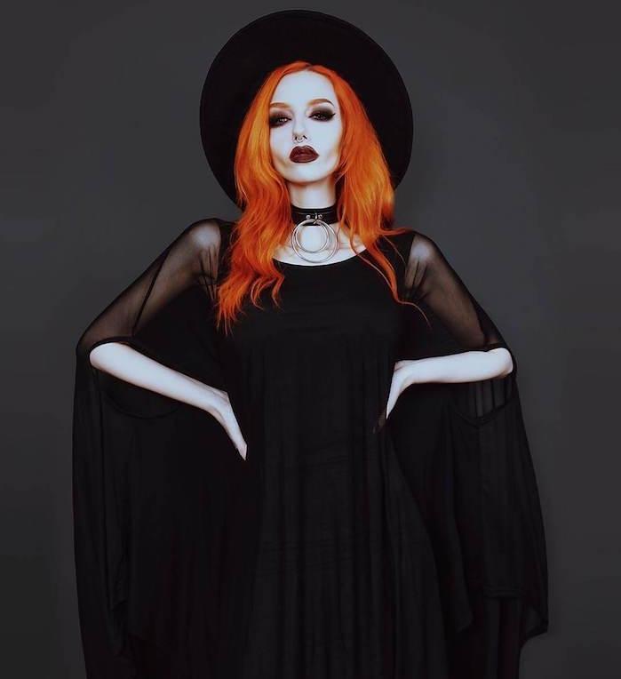 cheveux coloration rousse, robe longue noire à manches longues évasées, collier ras du cou, maquillage foncé, rouge à lèvres bordeaux, capeline noire sorcière