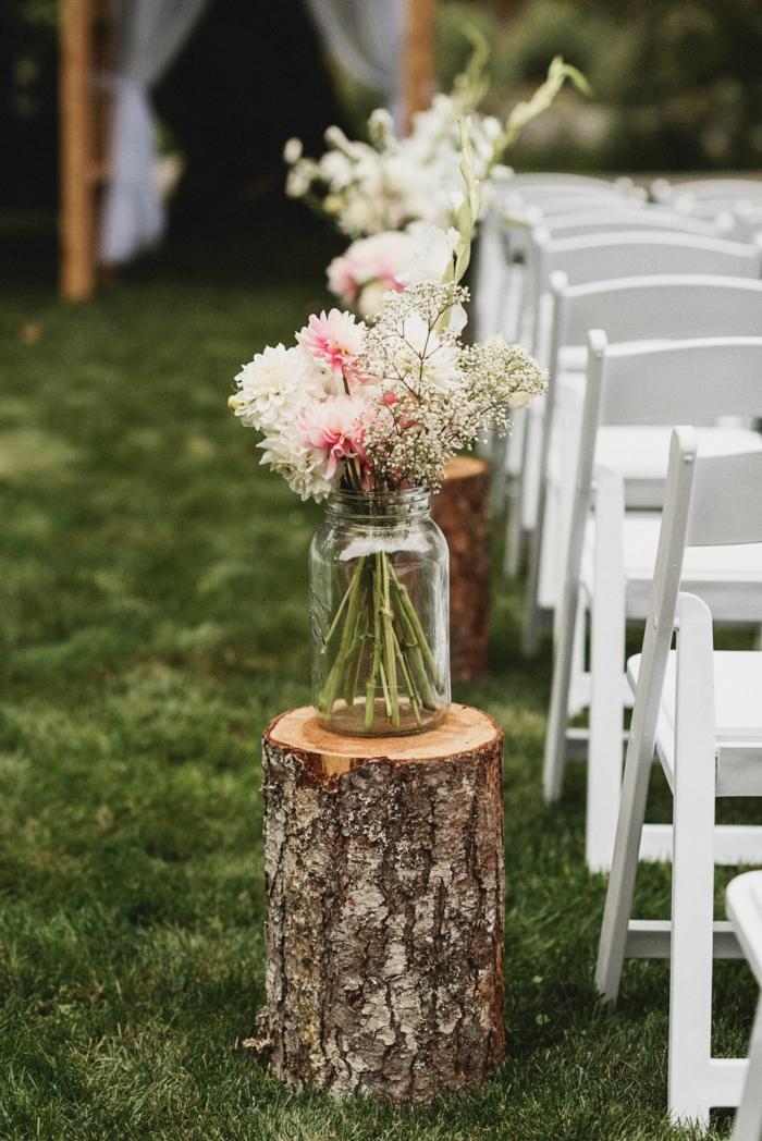 mariage theme champetre, pelouse verte, troncs de bois déco avec vases bocaux