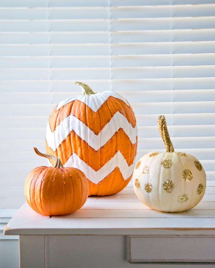 exemple de décor automnal avec citrouilles peintes en blanc et orange à motifs dorés, comment décorer une citrouille avec strass et paillette