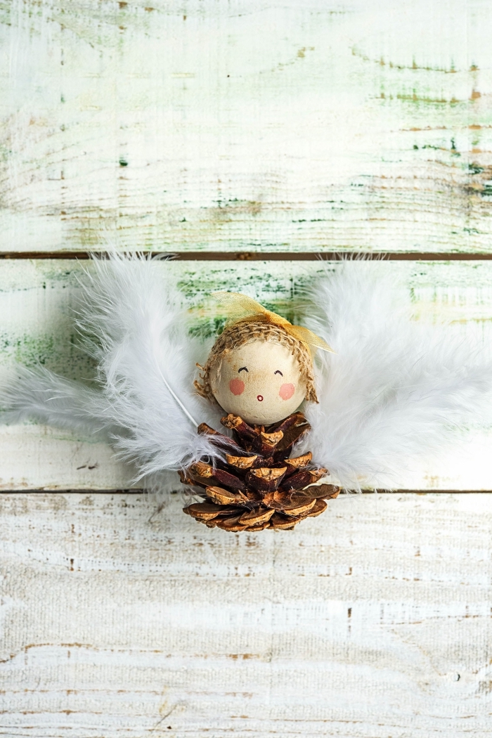 idée pour faire une figurine en pommes de pin et perle de bois à visage dessiné, figurine ange aux ailes en plumes blanches et corps en pomme de pin