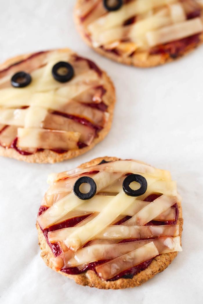 des minis pizzas apéritives à la tomate et au fromage vegan en forme de petites momies d'halloween, bouchées apéritives pour un repas halloween aussi savoureux qu'effrayant