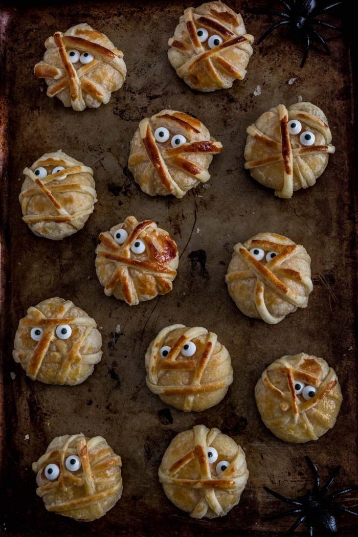 des bouchées apéritives au fromage enrobées de pâte feuilletée façon momies d'halloween, idée originale pour un apéritif halloween
