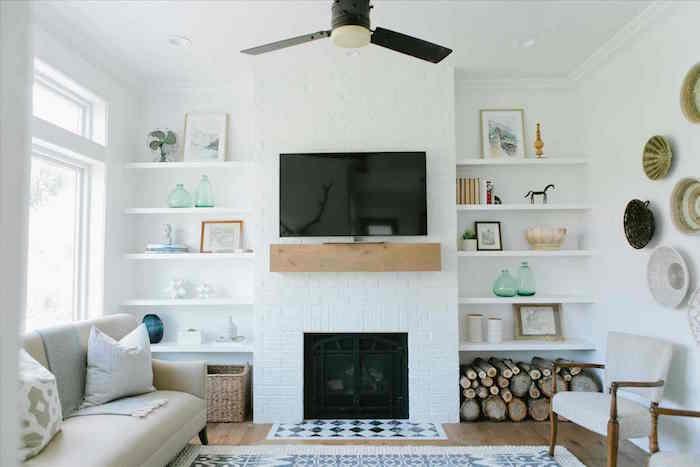 cheminée fermée moderne incrustée avec cadre blanc et étagère poutre bois comme support tv, murs blancs avec étagères et plats suspendus