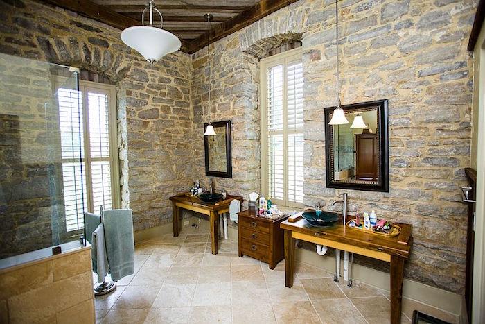 murs de salle de bain en pierres apparentes avec mortier restauré et plafond en bois, double meuble lavabo bois avec receveur vasque