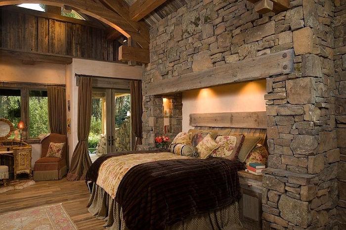 chambre style chateau moyen age avec murs en vieilles pierres grises différentes formes et lit dans cadre de cheminée et charpente en bois