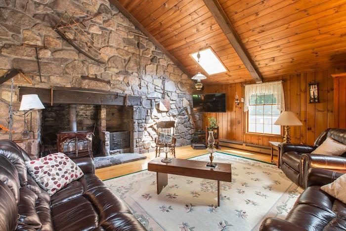 salon avec plafond mansardé en bois et mur en pierres apparentes en cadre de cheminée