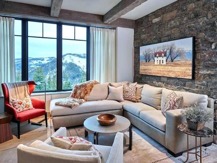 salon de chalet à la montagne avec mur intérieur en pierre et poutres apparentes en bois et canapé d'angle
