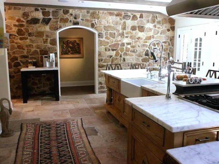 mur en pierre intérieur rénové à la chaux dans grande cuisine avec ilot central