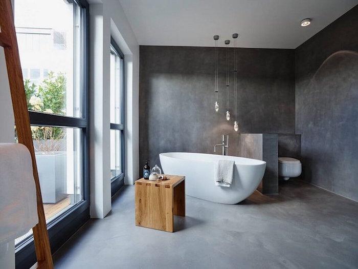 salle de bain avec revetement béton ciré sol et murs avec baignoire ilot blanche et tabouret en bois, coin toilettes avec mur séparateur