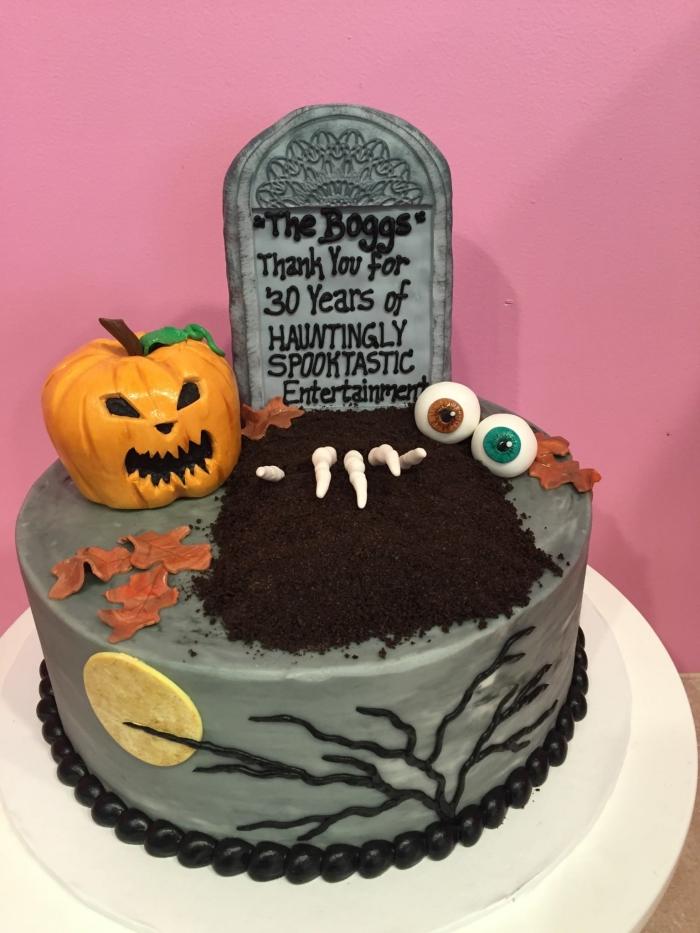 modèle de gâteau effrayant sur étage au nappage gris avec décoration en figurines plastiques ou en fondant coloré