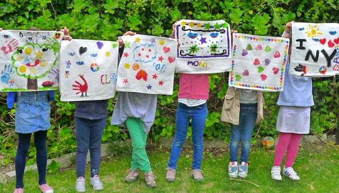 atelier créatif enfant pour créer une nappe personnalisée de dessins enfant en peinture motifs variés, idée jeux anniversaire imagination créativité