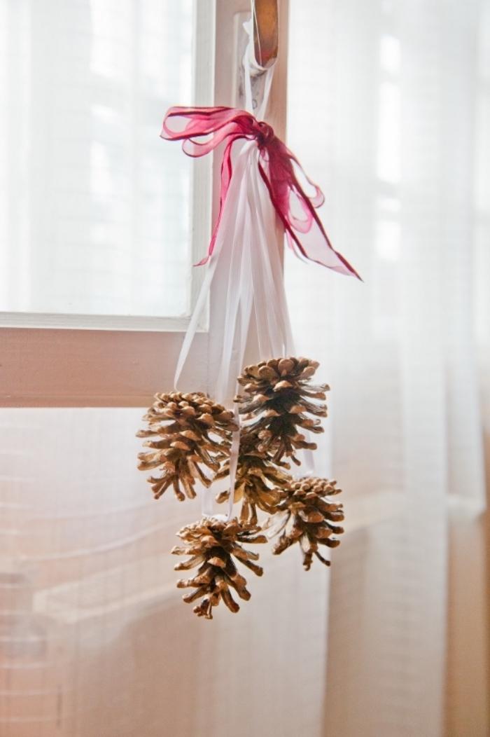 exemple de deco avec pomme de pin, fabriquer une suspension avec ruban et pommes de pins colorées en or