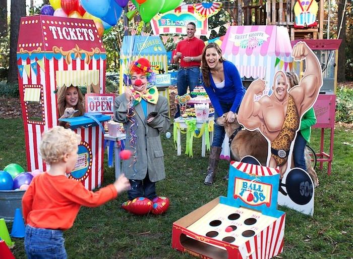 theme anniversaire parc d attraction ou cirque sur un gazon vert avec des divertissements et jeux enfant thematiques, enfant déguisé en clown