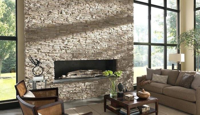 pierre de parement beige recouvrant mur et conduit de cheminée dans grand salon avec baies vitrées