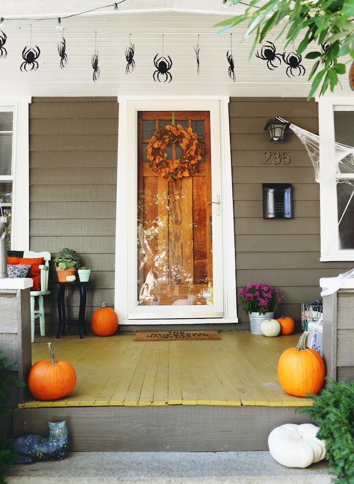 décoration halloween extérieur a fabriquer en citrouilles, couronne de feuilles mortes et des araignées suspendus en papier