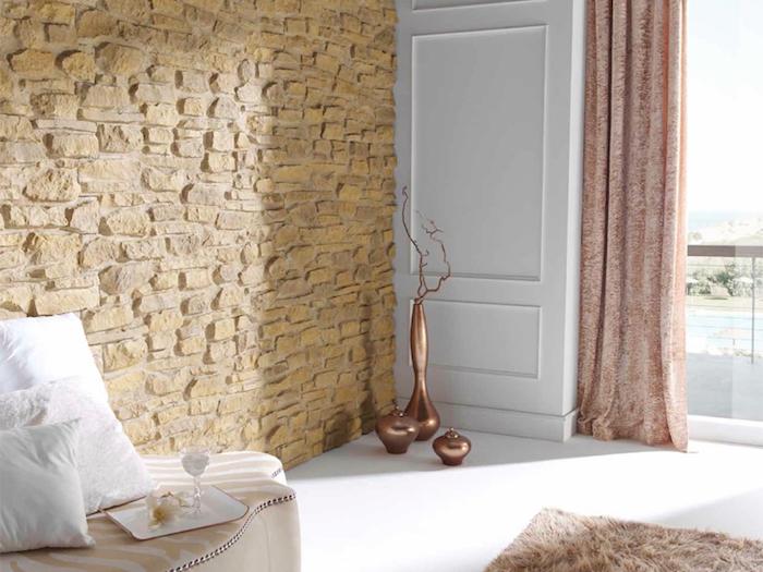 salon ou chambre claire avec sol blanc et mur en pierres de parement beiges