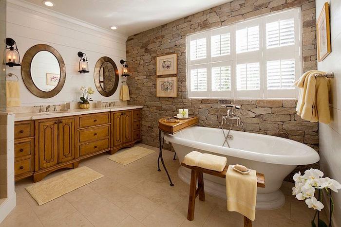 salle de bain à la déco vintage avec baignoire ilot et mur imitation pierres
