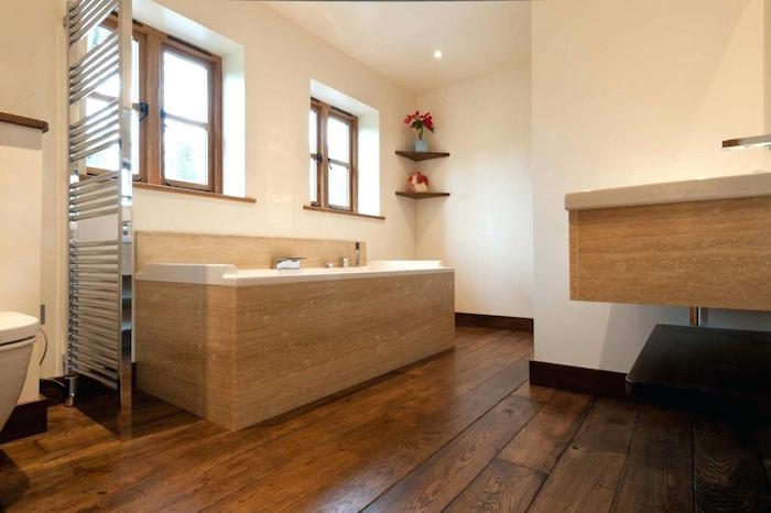 sdb sur parquet en bois foncé avec cadre baignoire beige et mur blanc