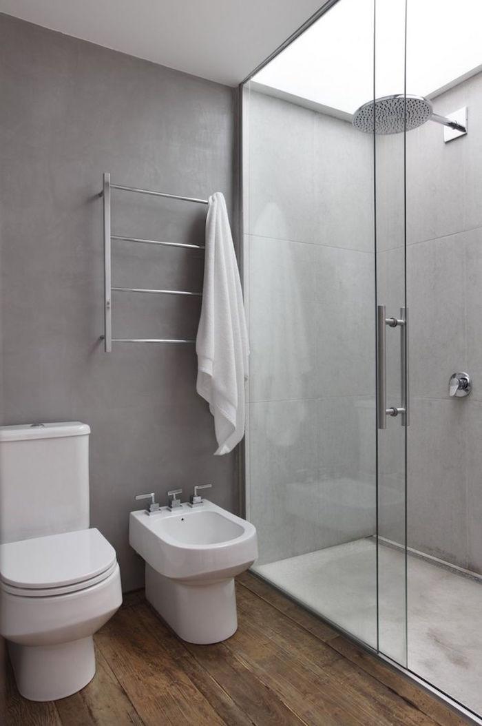 salle de bain avec murs en béton ciré ciment, douche italienne et sol en parquet avec toilettes et bidet