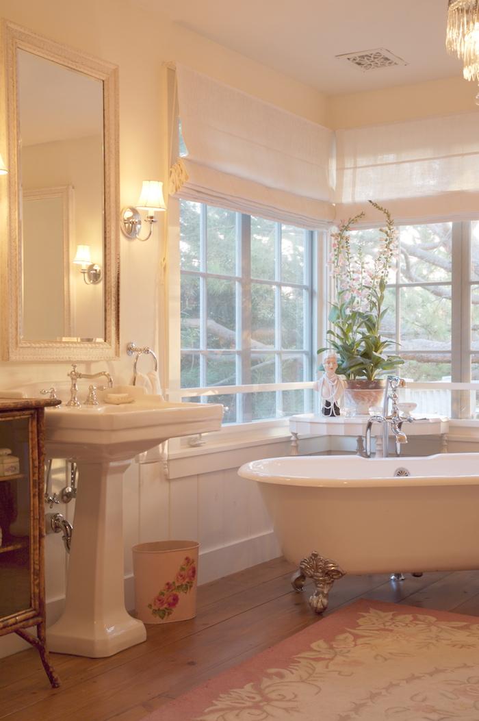 grande salle de bain avec parquet et style classique avec baignoire ilot sur pied argent dans l'angle, murs blancs