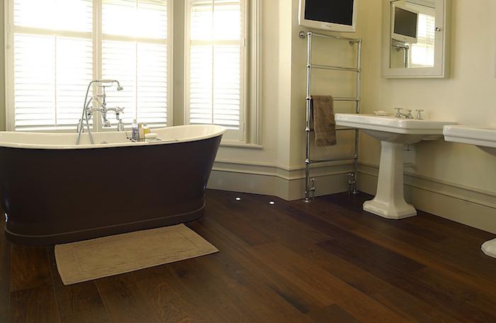 salle de bain sir parquet foncé avec baignoire ilot marron et double lavabo rétro