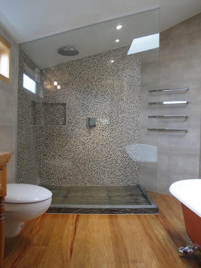 salle de bain moderne mansardée avec mur en ciment gris, douche italienne et sol en bois avec baignoire ilot