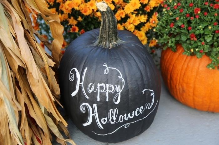 exemple de décoration extérieure pour la fête d'Halloween avec citrouille peinte en noire à lettres blanches