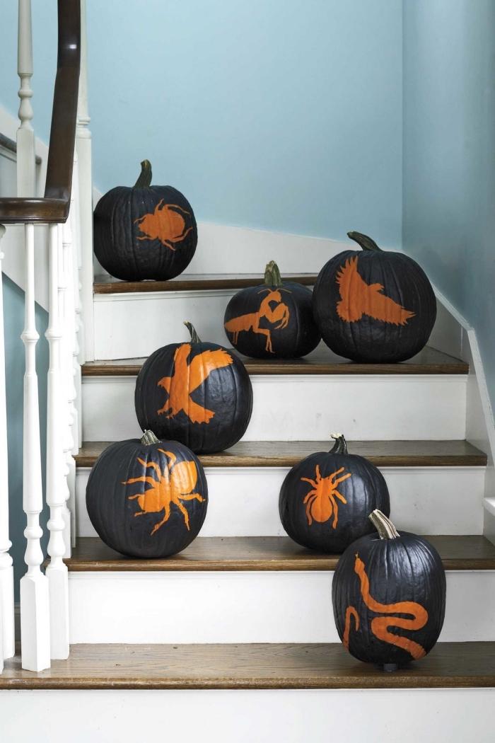 idée comment décorer un escalier intérieur pour la fête d'Halloween avec citrouille peinte en noir à déco dessins effrayants