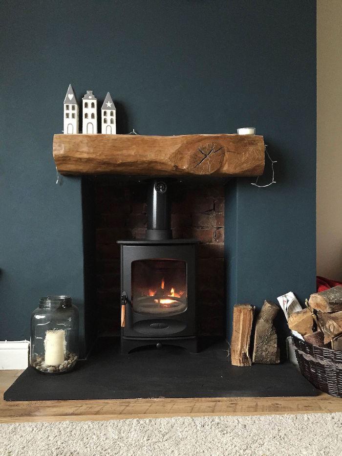 rénover et relooker une cheminée avec poele à bois, mur couleur bleu paon et étagère en bois et déco minimaliste