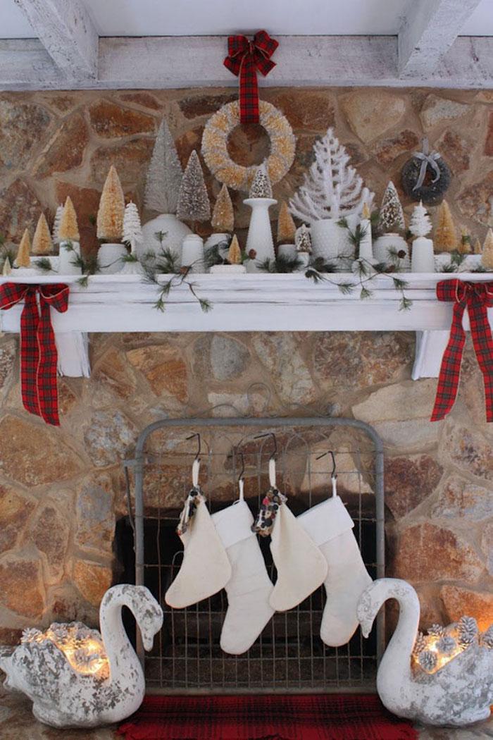 deco de noel sur cheminée en pierres avec étagère blanche en bois et objets decoratifs chaussettes, bougies et mini sapins