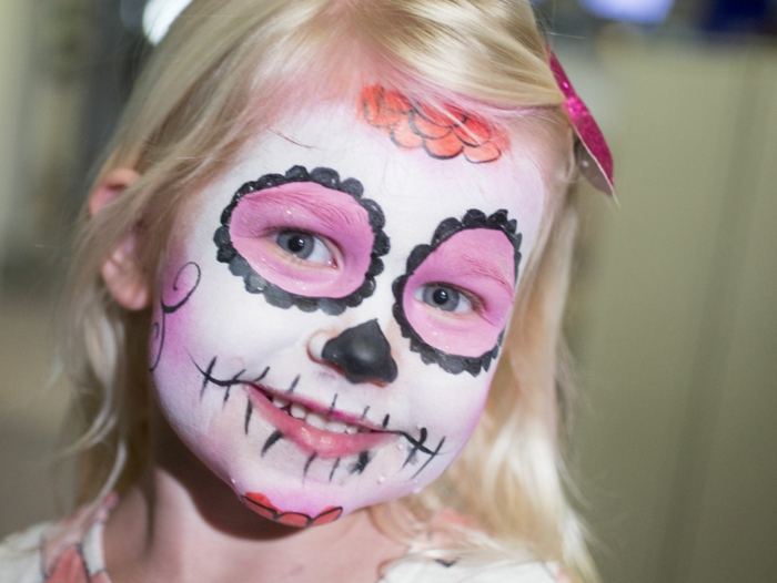 maquillage halloween mexicain, petite fille blonde avec un maquillage squelette rose et noir