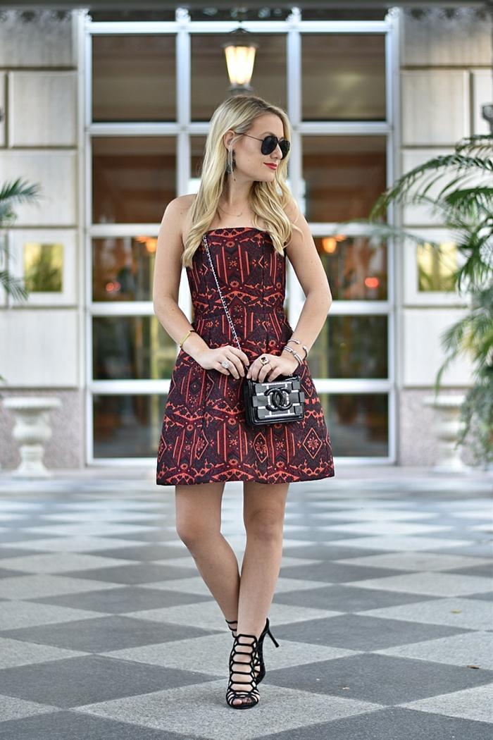 robe aux imprimés ethniques, pochette noire avec chaîne, sandales hautes, lunettes de soleil, cheveux bouclés