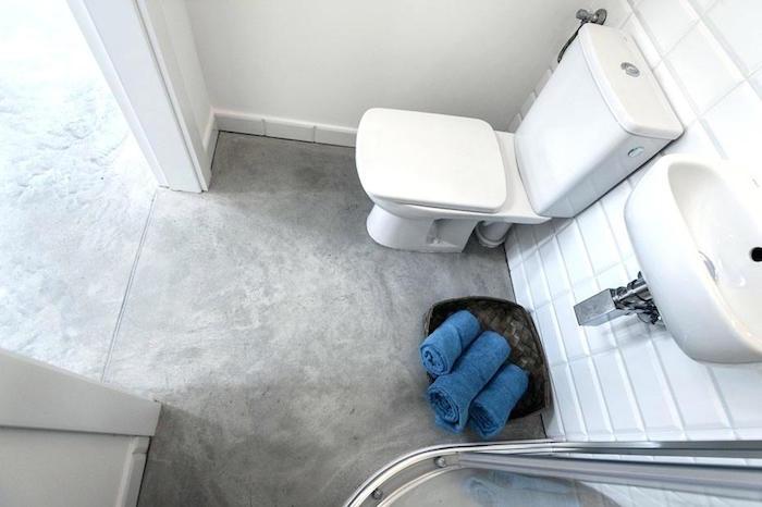 mini salle debain avec douche et toilettes et sol en béton ciré gris