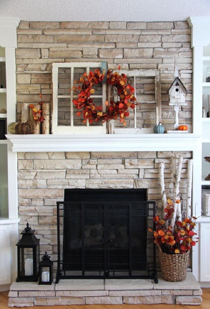 cheminée dans mur en pierre de parement avec support blanc pour objets déco rustique en bois et fleurs couleurs automne