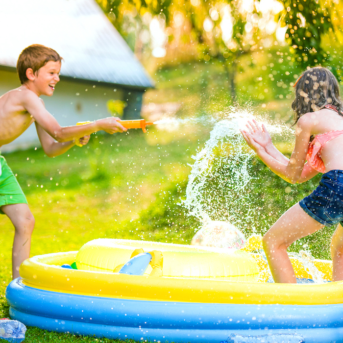 anniversaire 10 ans en plein air pendant l été, jeu avec des pistolet à eau autour d une piscine gonflable sur un gazon vert